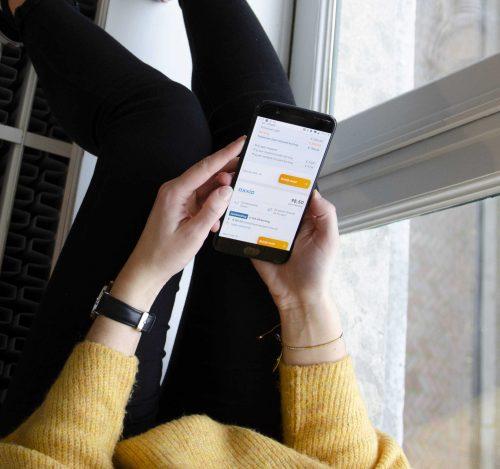 Vrouw liggend met telefoon voor energie vergelijken